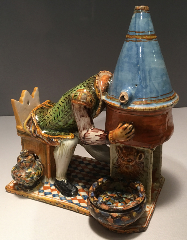 "Inkstand with A Madman Distilling His Brains. Italian, probably Urbino, ca. 1600. Tin-glazed earthenware. Metropolitan Museum of Art. The back of the chair is inscribed: ""I distill my brain and am totally happy."""